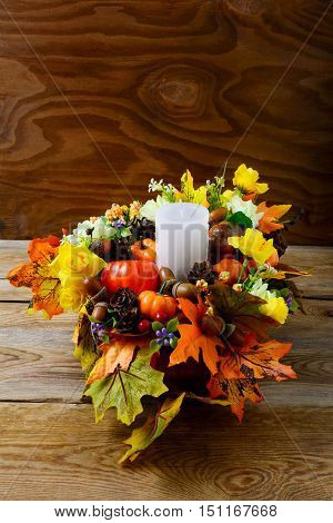 Fall table centerpiece with candle and silk maple leaves vertical. Thanksgiving greeting with fall decor. Fall centerpiece. Thanksgiving background.