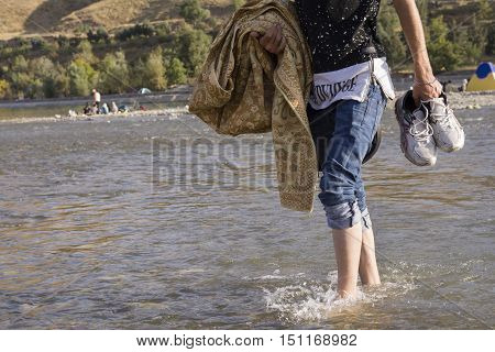 Tehran IRAN - September 12 2016 A Young Man Walking in Shallow Water by Bare Foots; Carrying Linen Cloth and Shoes By Hands