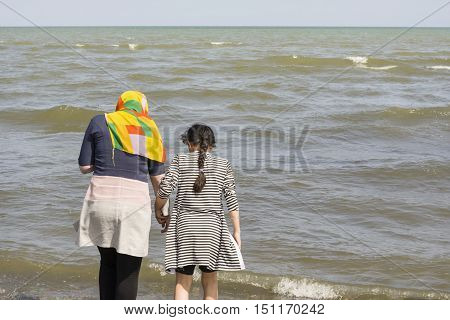 Astara- IRAN-September 22 2016 Back View of Two Young Ladies Standing on The Beach Caspian Sea Shore Gilan Province.