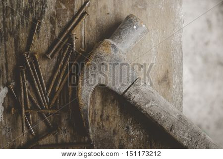 old hammer with rusty nails on wood table background vintage style