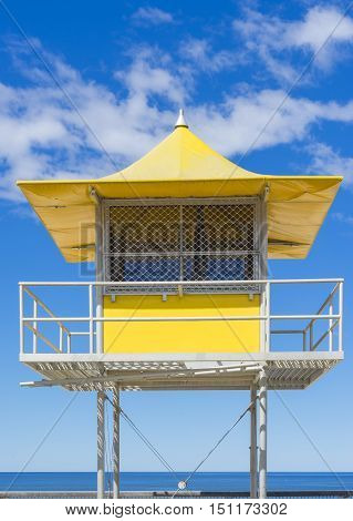 Bright yellow lifeguard patrol tower against the blue sky background