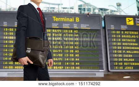 Business trip. Businessman with a briefcase on a background of departure board at airport