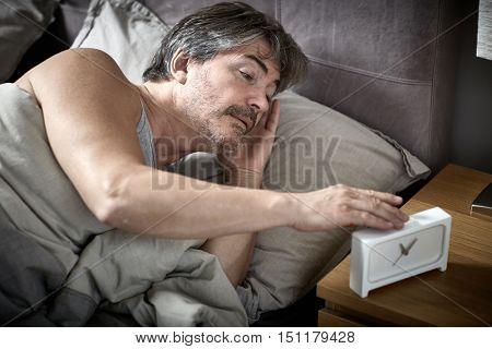 Sleepy man in bed wake up.