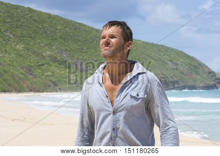 Rugged filthy Caucasian castaway man with beard and dirty shirt lost on deserted island beach under bright sun