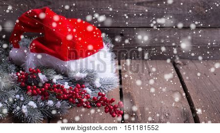 Christmas holiday composition with place for text. Santa hat branches fur tree and red berries on aged wooden background. Selective focus. Drawn snow.