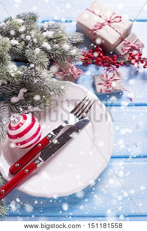Christmas table setting. White plate knife and fork napkin and christmas decorations in white and red colors on blue wooden table. Selective focus. Drawn snow.