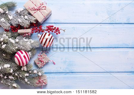 Border from christmas presents fur tree branches balls and red berries on blue wooden background. Selective focus. Top view. Place for text.