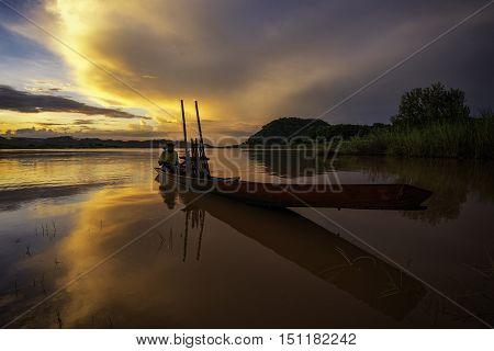Fishermen on boat fishing at lake in Thailand.