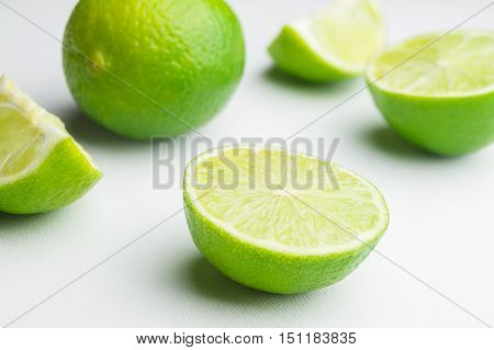 Green limes. Whole lime with slices isolated on white background. Halved limes.