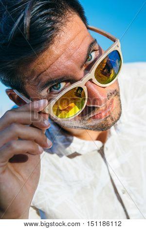 Portrait of stylish handsome brunet man looking over sunglasses