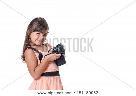 Smiling long hair little girl is holding SLR camera. The girl is slightly skewed and is looking at the camera. All is isolated on the white background. All potential trademarks are removed.