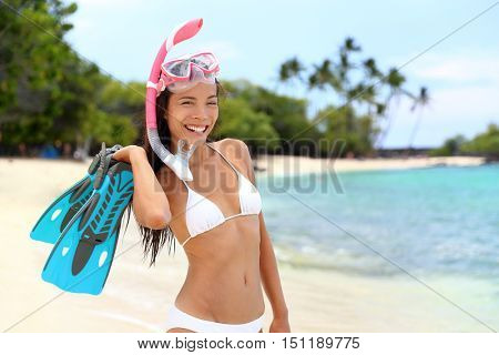 Snorkel girl on beach vacation getaway holding snorkeling gear: blue flippers wearing pink scuba mask and white bikini. Happy Asian woman relaxing in tropical destination with tuba and fins.