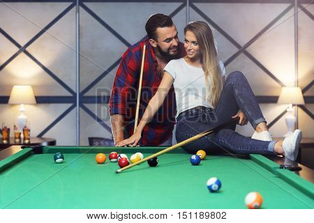 Picture of pretty couple playing billards