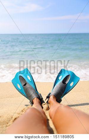 Foot selfie: snorkeler relaxing on beach overlooking the ocean with legs showing blue flippers snorkel equipment lying on sand. Tropical getaway vacation. Watersport fun activity: snorkeling.