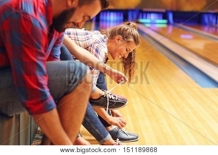 Picture showing friends putting on bowling shoes