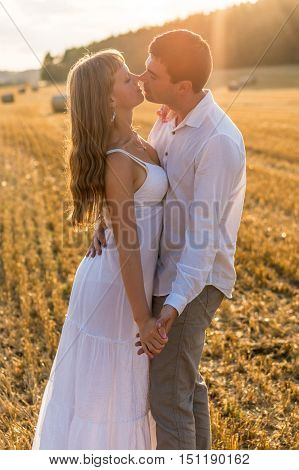 Young loving couple kissing in a field - passion and love concept