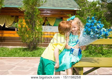 The boy gives a flower to a girl child on happy birthday. Celebration concept and childhood love