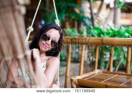 Beautiful brunette woman in long dress and hat relaxing near bar in exotic resort
