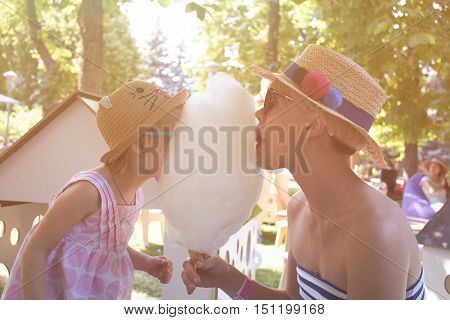 Child eats cotton candy with mom in city street. Effect retro film