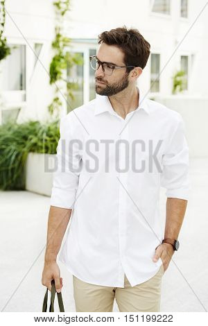 Man in white shirt and spectacles walking in town