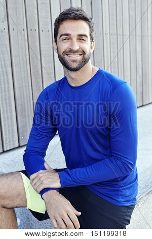 Athletic guy in blue smiling portrait - in town