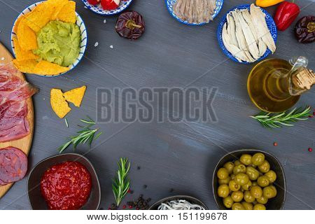 Table with spanish tapas - anchovies with peppers padron, jamon, croquetes, guacamole and olives, frame with copy space, picnic table