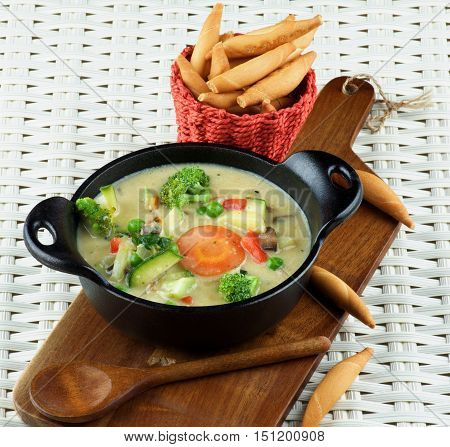 Homemade Vegetables Creamy Soup in Black Stewpot with Wooden Spoon and Bread Sticks on Wooden Cutting Board closeup on Wicker background