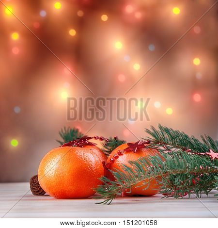 Mandarins with fir-tree branch with the background of garlands