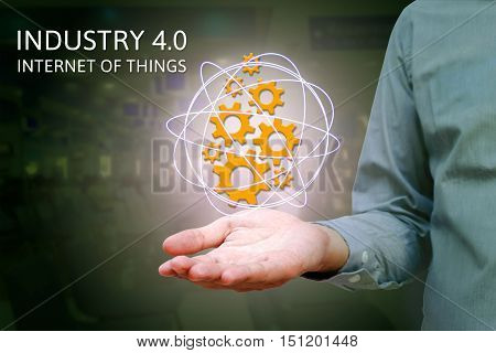 Industry 4.0 industrial internet of things concept with man show gears icons and network with factory background.