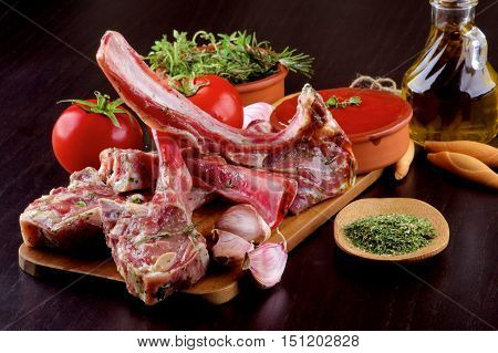 Arrangement of Raw Lamb Ribs with Tomatoes Spices Olive Oil and Garlic on Wooden Cutting Board closeup on Dark Wooden background