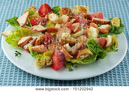 Delicious Caesar Salad with Roasted Chicken Breast Garlic Crouton Romaine Lettuce Cherry Tomatoes and Grated Parmesan Cheese closeup on White Plate on Blue Napkin