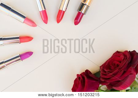 Collection of puple, pink and red shiny lipsticks and red roses, top view with copy space