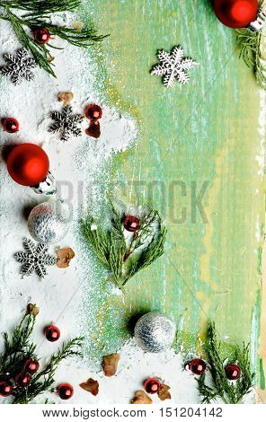 Christmas Greeting Background with Border of Green Branches Snow Flakes Red Baubles and Silver Stars closeup on Cracked Wooden background
