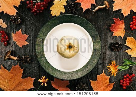 Vintage plate in the frame of fall leaves and fruits. Flat lay