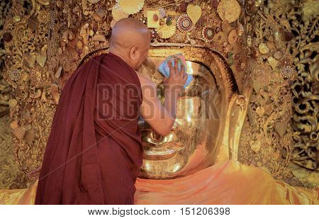 MANDALAY, MYANMAR - DECEMBER 2015: Mahamuni Buddha image is being worshiped by the head monk; part of a daily washing ritual in Mahamuni temple, Mandalay, Myanmar.