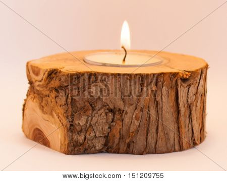 wooden candlestick with a burning white candle