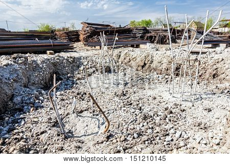 Skeleton of reinforcing steel armature bar at construction site is buried into ground filed with concrete.