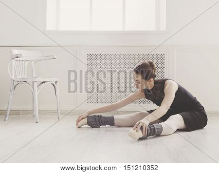 Classical Ballet dancer portrait. Beautiful graceful ballerine in black practice stretching in class room background. Ballet class training, high-key soft toning.