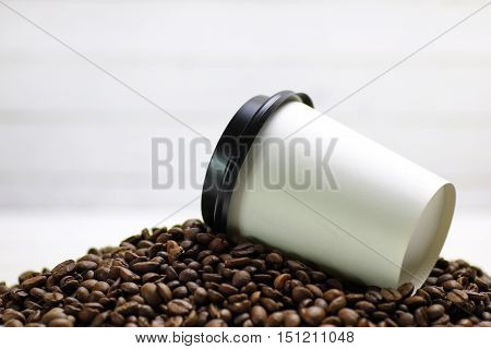 coffe paper cup and beans on white background