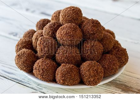 White plate with brown candies. Sweets covered in crumbs. Chocolate balls on wooden table. Cocoa powder and butter.