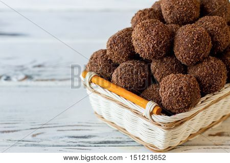 Dark colored sweets with crumbs. Desserts in a basket. Special recipe of chocolate balls. Mixture of cocoa and biscuits.