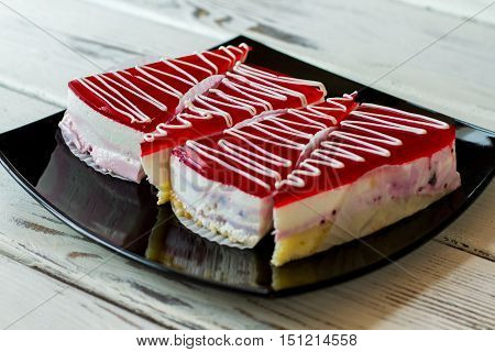 Pieces of cake on plate. Layer of jelly. Dessert with currant mousse. Sweet treat from the shop.
