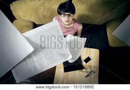 Image of tired business woman with flying papers around her. On the table next to her laptop smartphone glass of water.