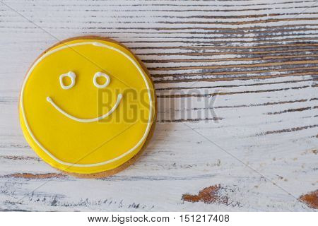 Smiley biscuit on wooden surface. Round cookie with icing. Charge of mood and energy. Don't forget to eat dessert.