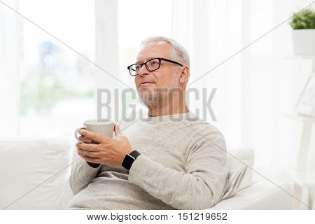 old age, drink and people concept - happy senior man with cup of tea at home