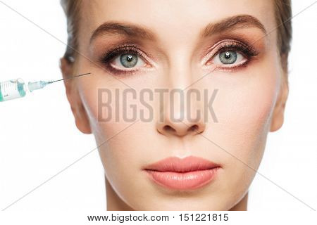 people, cosmetology, plastic surgery, anti-aging and beauty concept - beautiful young woman face and syringe making injection to eye area over white background