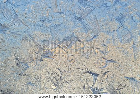 pattern of frost on the glass in the golden-blue tones