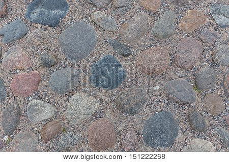 old stone masonry road. stone texture close-up part of the road made of cobblestones