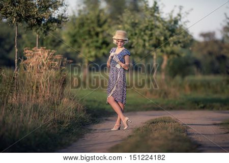Retro 1920S Summer Fashion Woman With Blue Dress And Straw Hat Standing On Rural Road.
