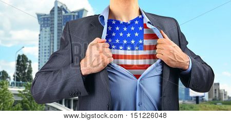 Yong businessman showing USA flag under suit on blurred building background.